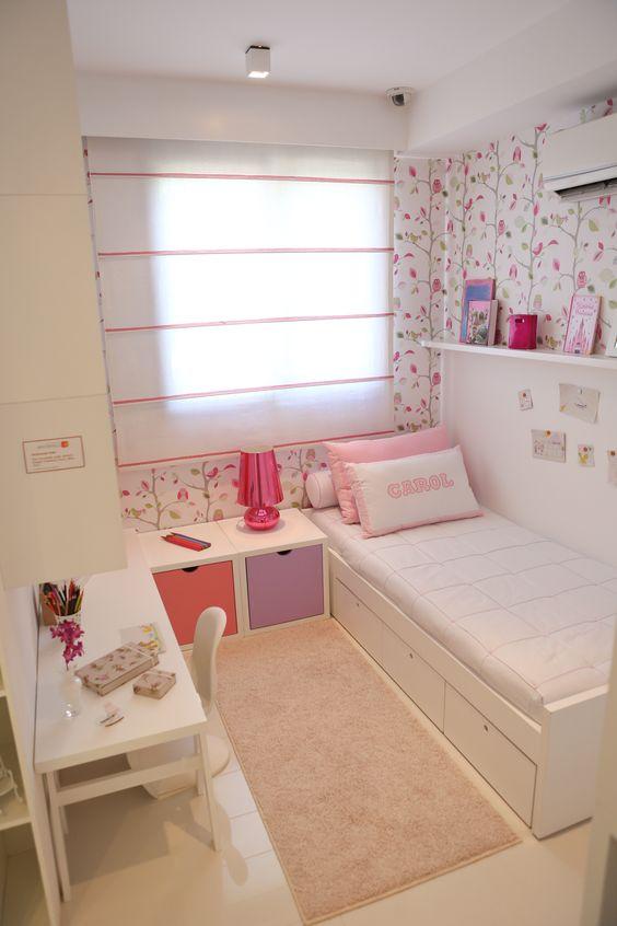 Decoração de quarto de menina com papel de parede florido e gavetas coloridas.