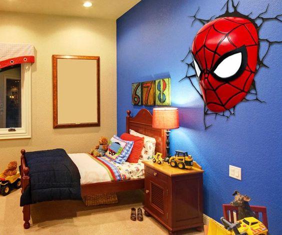 Quarto de menino com cama, mesinha de cabeceira e papel de parede 3D com o rosto do Home Aranha.