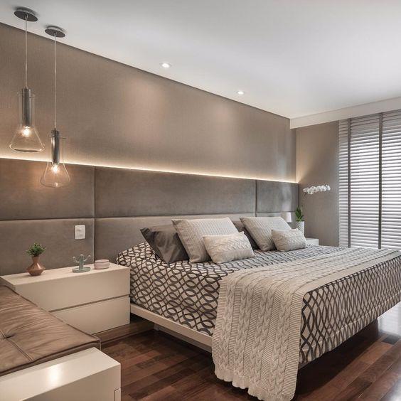 Cabeceira de cama iluminada em quarto de casal moderno.