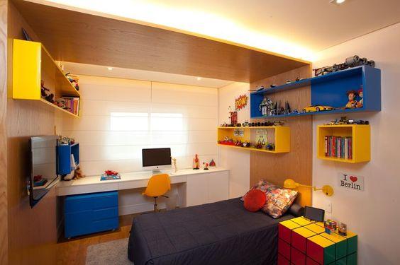 Decoração de quarto colorido com mesa, cama e mesinha de cabeceira em formato de cubo mágico.