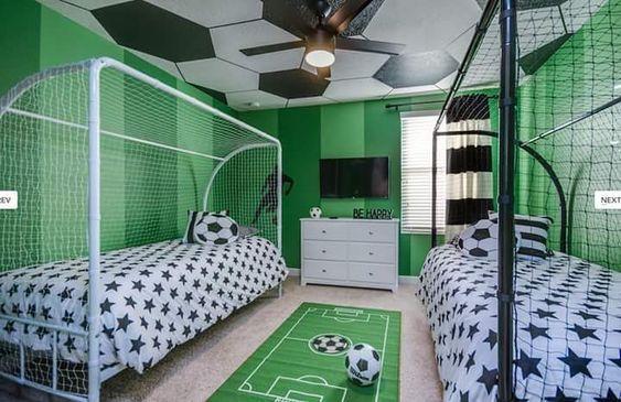 Decoração de quarto com tema de futebol com duas camas dentro de gols.