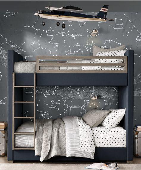 Decoração de quarto com beliche e papel de parede com as constelações e um avião suspenso.