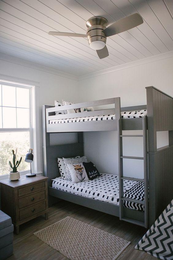 Decoração de quarto de meninos simples com beliche e roupa de cama em preto e branco.