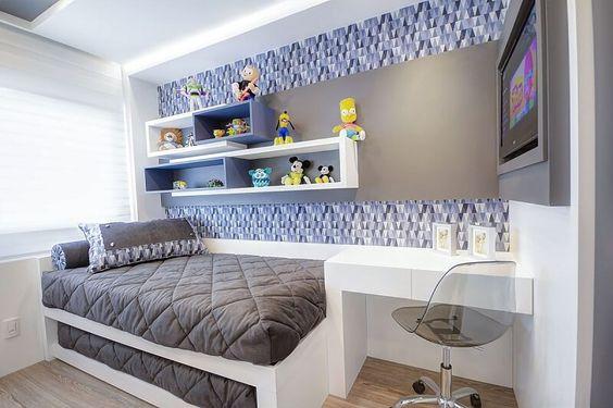 Decoração de quarto de menino com cama, nichos, mesa e cama reserva.