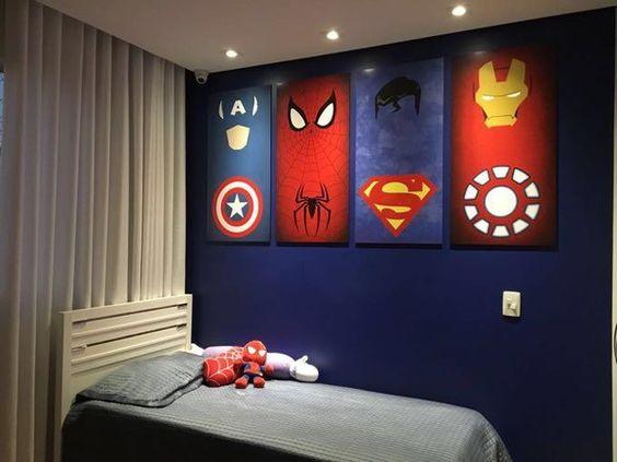 Decoração de quarto com iluminação direcionada em quadros de super-heróis na parede.