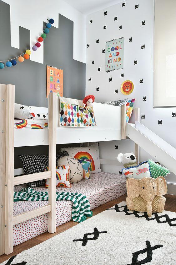 Decoração de quarto com cama com escada e escorregador e cama reserva.