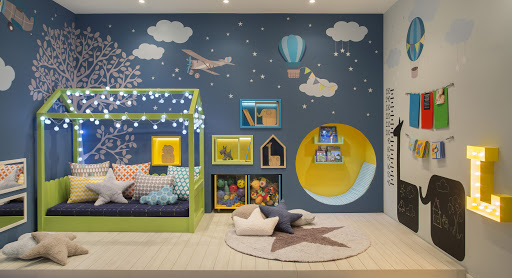Decoração de quarto de menino com papéis de parede, lousa, nichos e cama iluminada.