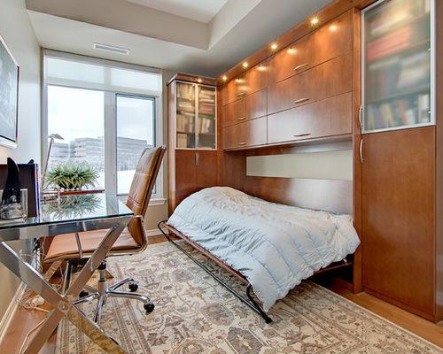 Decoração de quarto de hóspedes com cama que vira guarda-roupa e mesa de vidro.