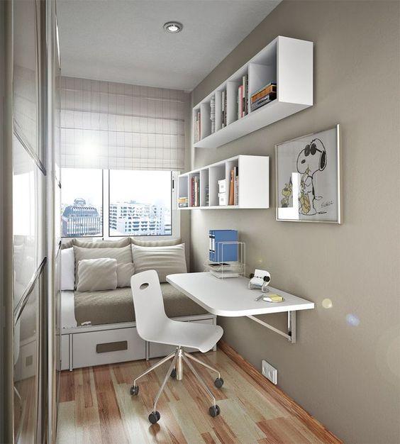 Decoração de quarto de hóspedes pequeno com mesa, cama, guarda-roupa e nichos.