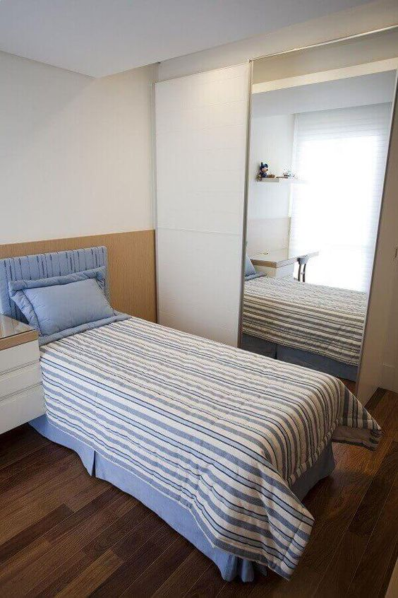 Quarto minimalista com porta de guarda-roupa espelhada e cama de solteiro.