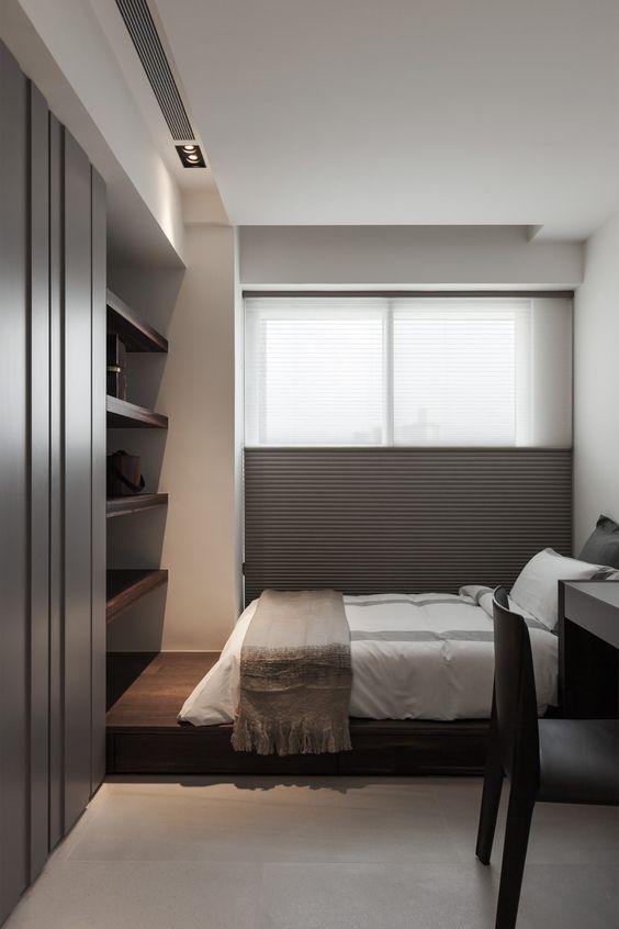 Quarto moderno em preto e branco com cama, prateleiras e mesa.