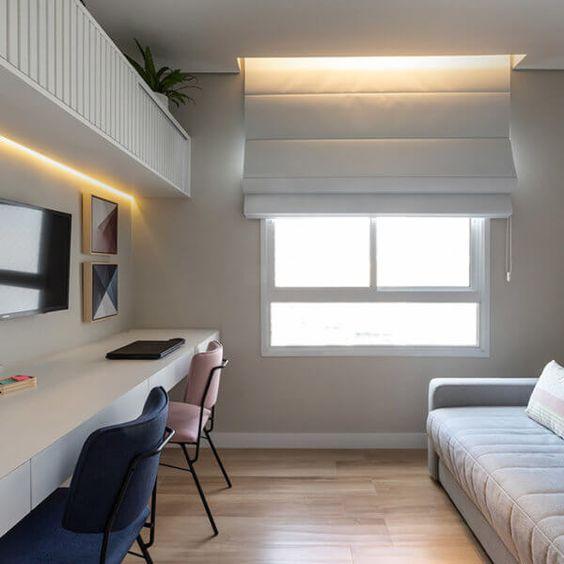 Decoração de quarto simples com mesa, duas cadeiras e uma cama.