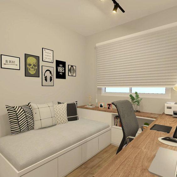 """Quarto com mesa em """"L"""", cama e quadros pendurados na parede."""