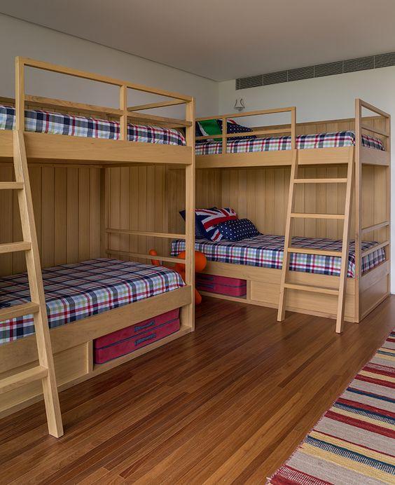 Duas beliches de madeira em quarto de hóspedes.