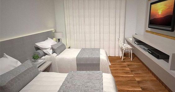 Decoração de quarto com duas camas de solteiro uma televisão embutida em painel.