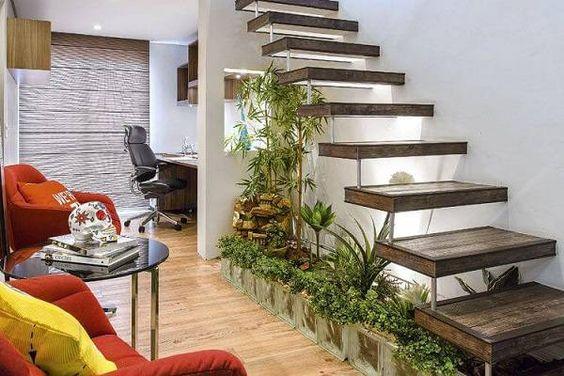 Jardim de inverno sob a escada reta tem divisória de tijolo de vidro.