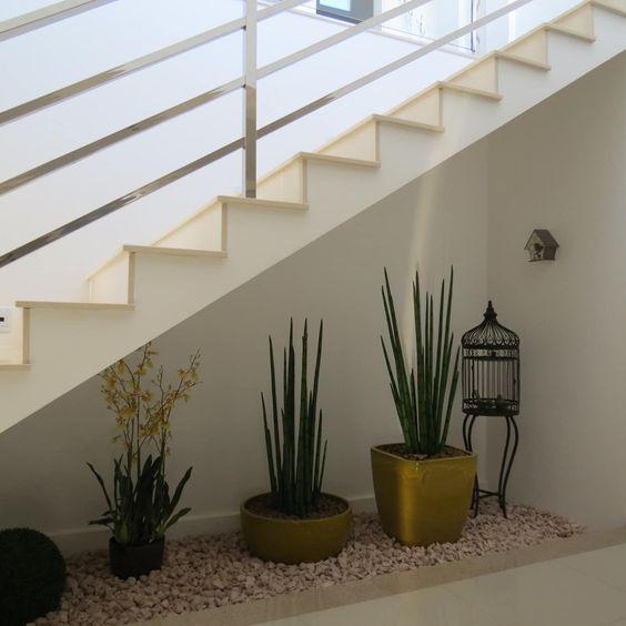 Vasos posicionados sob escada formam uma área verde no interior do sobrado.