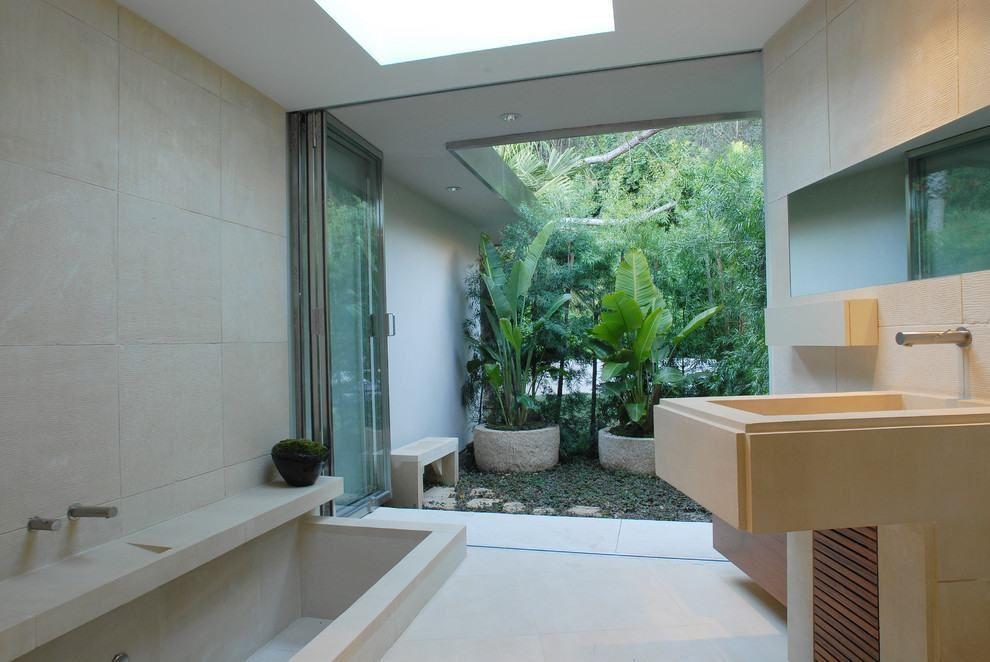 Com abertura por uma porta de vidro, banheiro traz lindo jardim ao fundo.