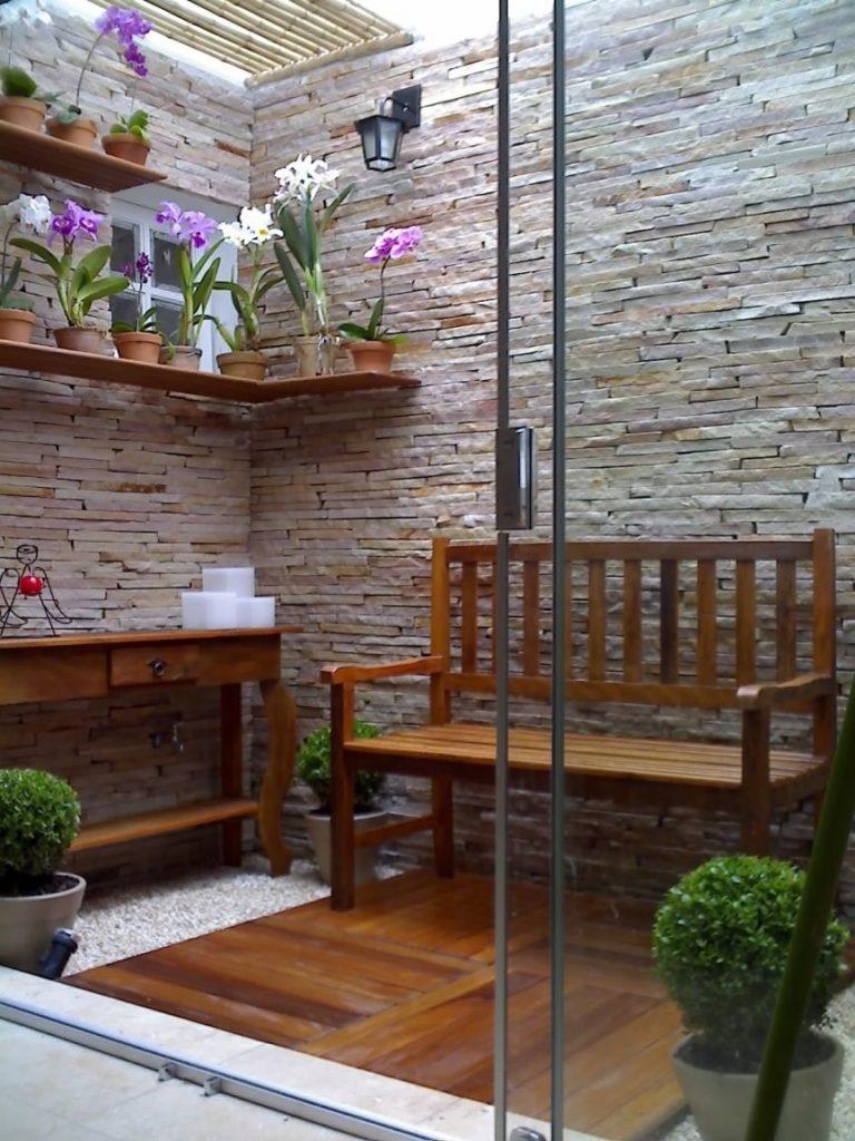 Jardim de inverno com área para plantas e espaço para descanso.