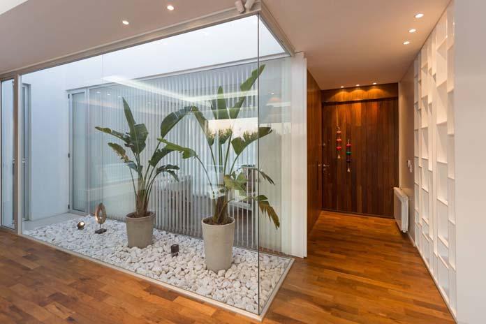 Sala com jardim de inverno em uma espécie de caixa de vidro.