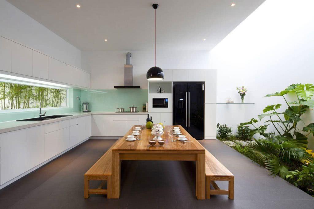 Cozinha com abertura externa ampla em frente a mesa de refeições.