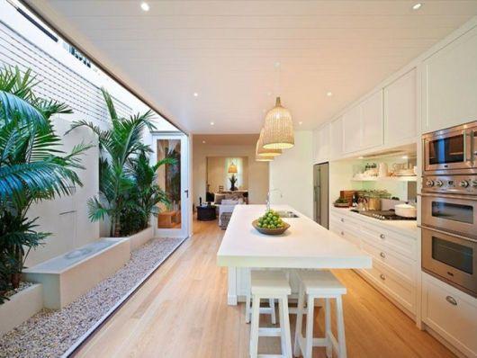 Cozinha com abertura externa com banco e canteiros.