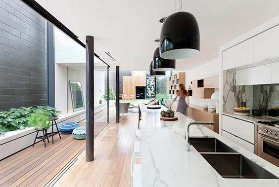 Cozinha com abertura externa com deck de madeira e canteiro.