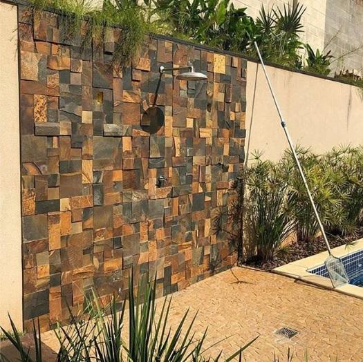 Ducha com parede feita de pedra ferro.