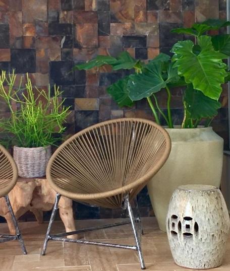 Detalhe de parede de pedra serrada com cadeira moderna na frente.
