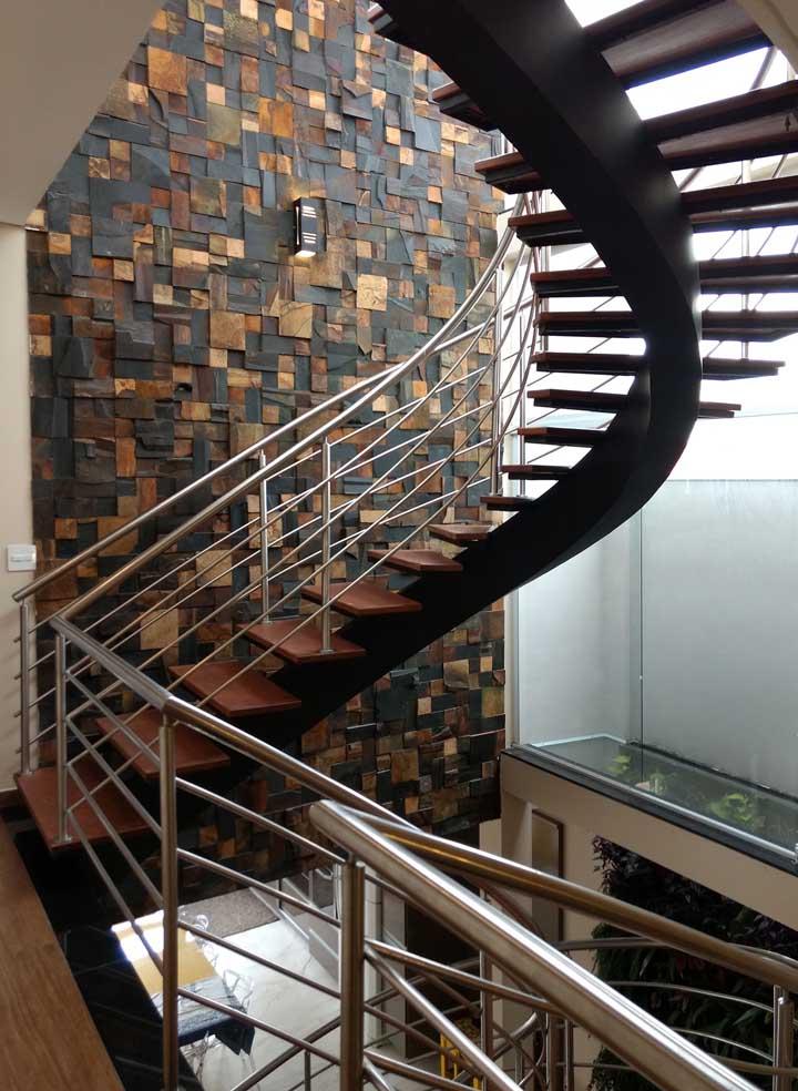 Escada de madeira ao lado de parede com pedra.