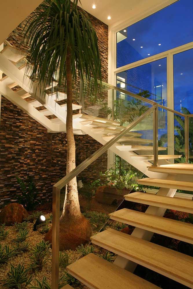 Ambiente com jardim interno e escada e parede de pedra pericó.