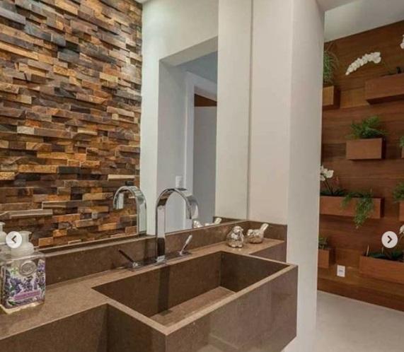 Banheiro com parede de pedra ferro.