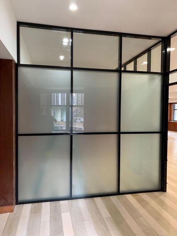 Divisória de vidro jateado.