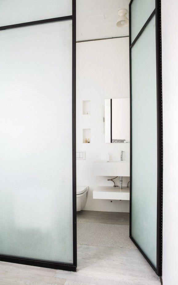 Porta de banheiro feita com vidro.