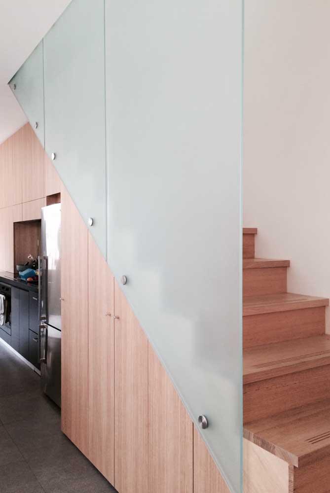 Escada com corrimão de vidro.