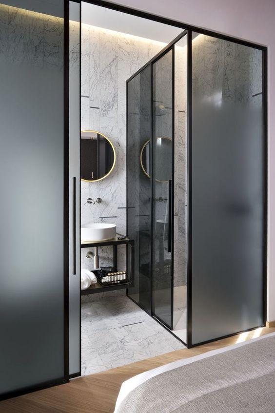 Banheiro com divisória de vidro.