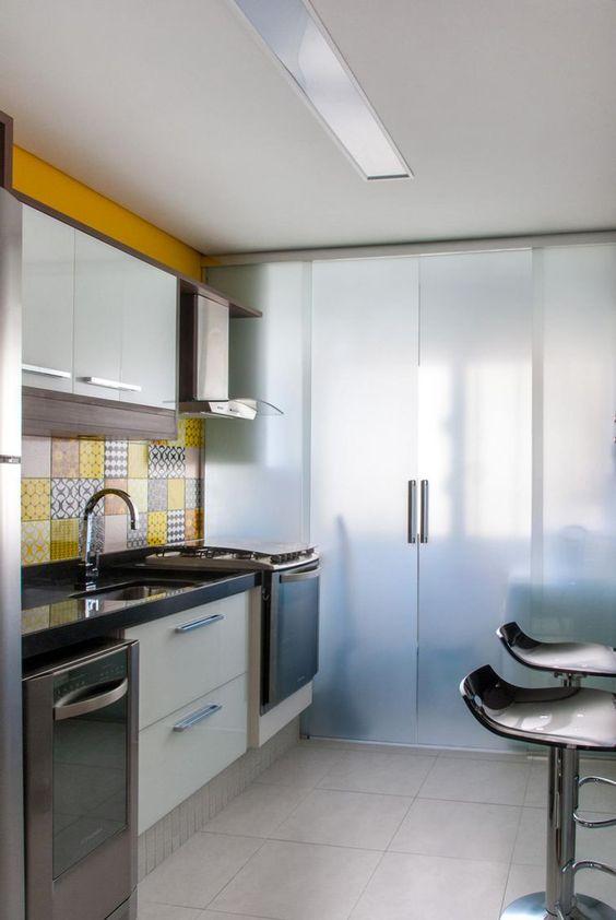 Cozinha com divisória de vidro.