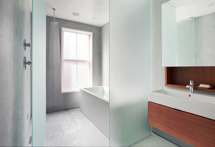 Banheiro com divisória de vidro jateado.