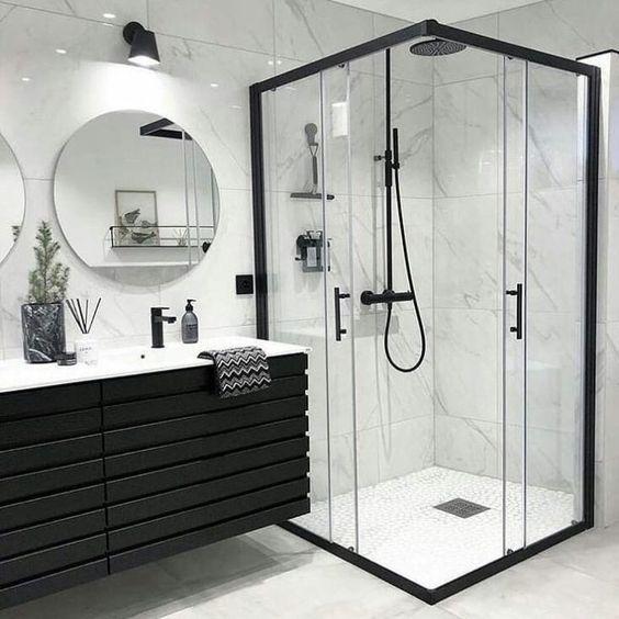 banheiro masculino preto e branco com box de vidro