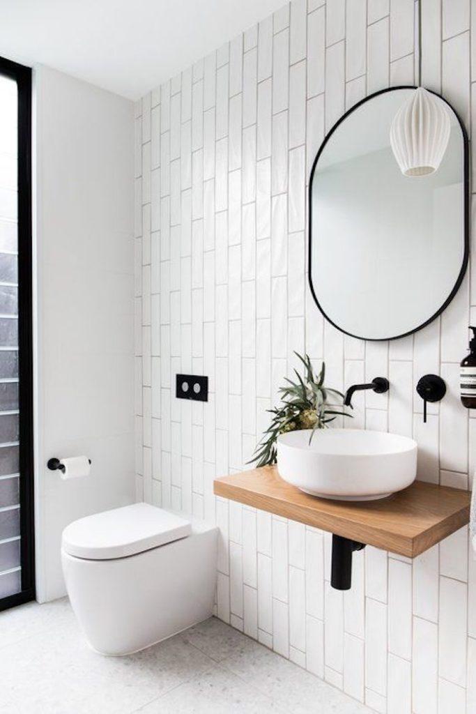 Banheiro branco com revestimento retangular em uma parede