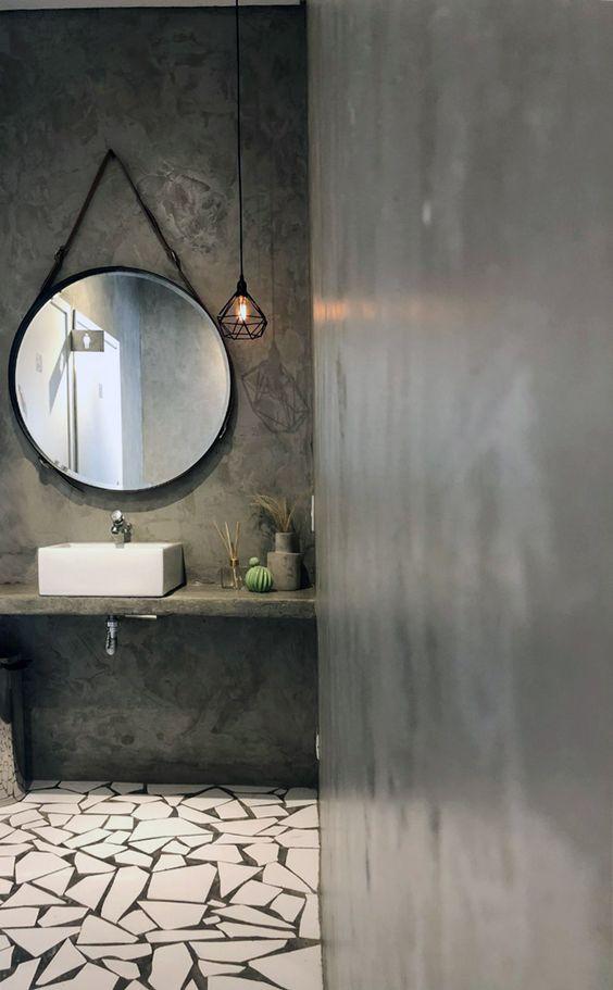 banheiro com paredes e bancada em cimento queimado