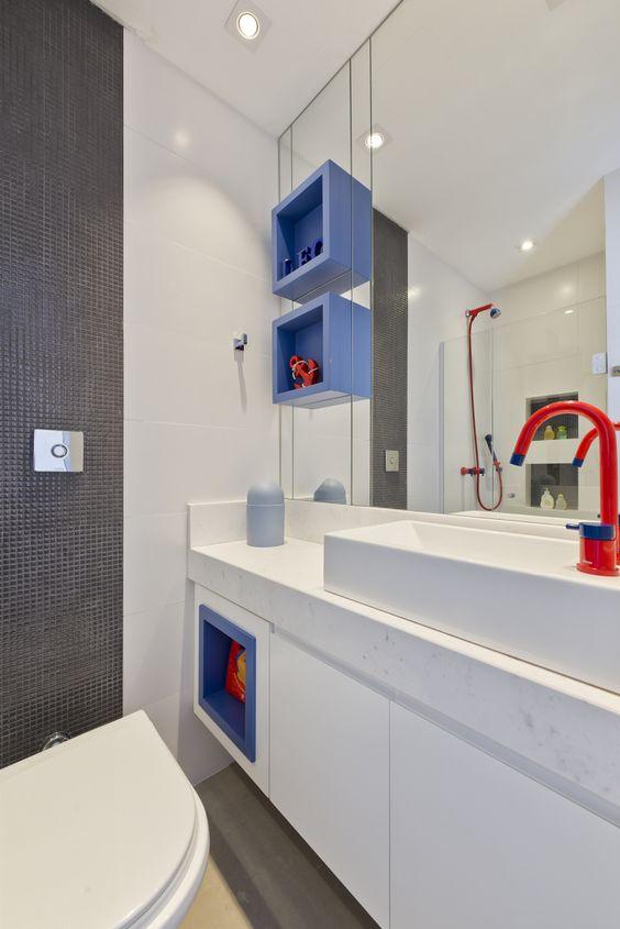 Banheiro com nicho azul e torneira vermelha.