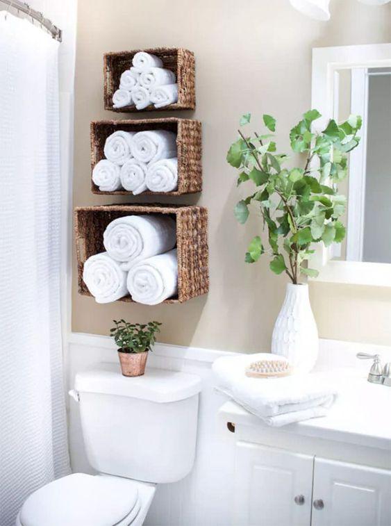 Banheiro com nicho decorado com toalhas brancas de diferentes tamanhos.