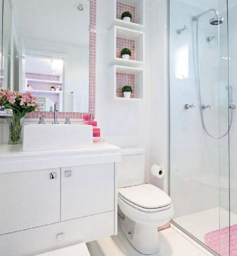Banheiro com nicho branco, fundo rosa e com vasinhos de plantas.