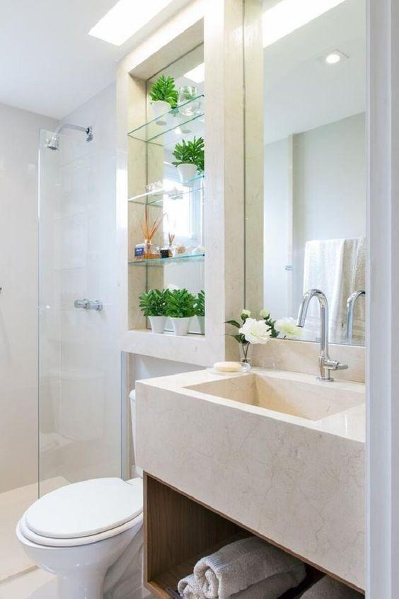 Nicho decorado com fundo espelhado em banheiro de cores neutras.