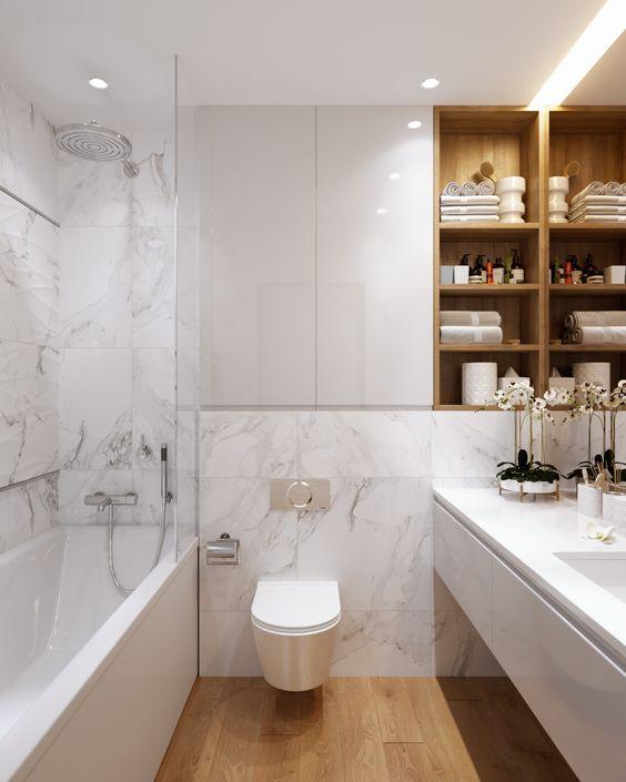 Banheiro organizado e decorado com nichos de madeira e vaso com flores.