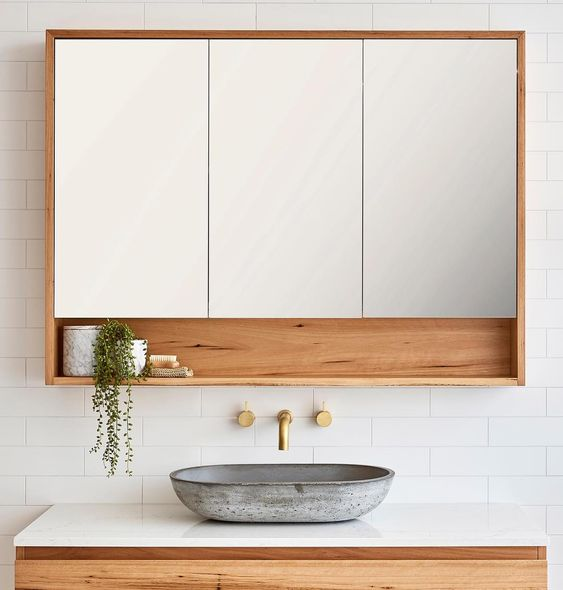Banheiro com nicho acoplado em armário de três portas espelhadas.