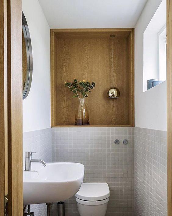 Banheiro com nicho grande embutido de madeira com vaso de planta e luminária prata.