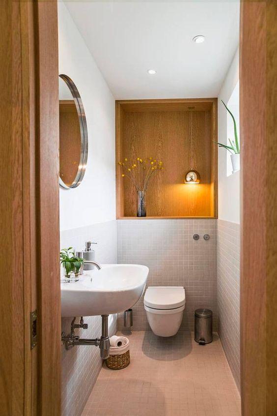 Banheiro com iluminação dentro no nicho de madeira.