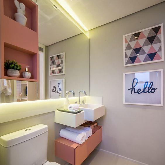 Banheiro decorado com quadros e nichos rosas.